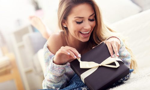 Picture showing woman opening present on carpet